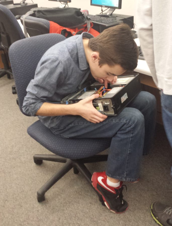 Caleb Smith, Computer Building Club president and freshman, checks a computer's ability to boot up. This procedure is part of the repurposing process.