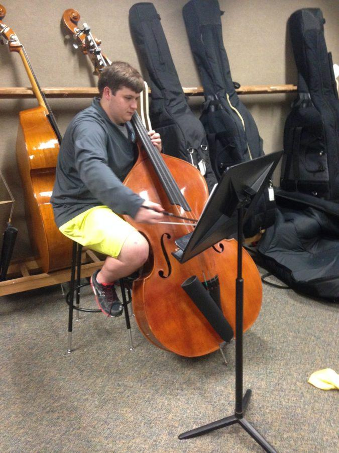 Sam Thomas, Symphony Orchestra member and senior, practices his bass after school before in the orchestra room. Thomas said he is going on the Vienna trip.