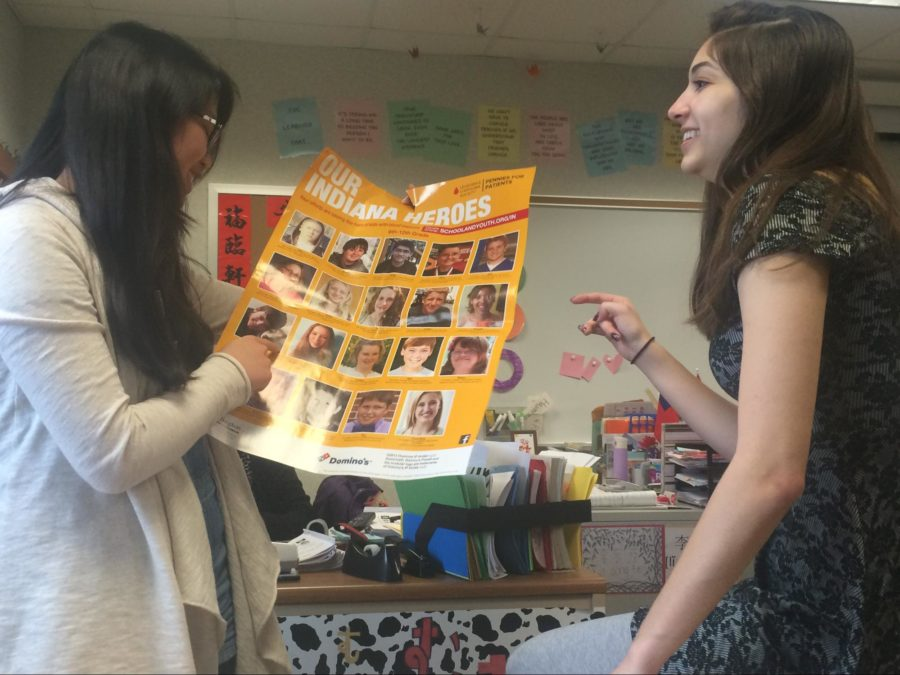 Co-presidents+and+seniors+Ally+Poveromo+and+Joie+Li+discuss+fundraising+events.+As+they+look+at+pictures+of+patients+who+had+leukemia%2C+they+think+of+ways+to+convey+the+importance+of+helping++those+children+to+club+members.