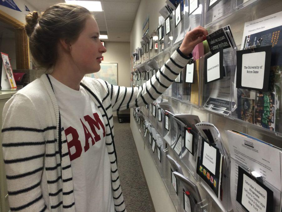 Senior Emily Shady looks at potential scholarships on the scholarship wall located in the counseling office. Scholarship Night, on May 23, will honor those, like Shady, who have received scholarships for college. NAOMI REIBOLD / PHOTO