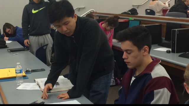 Caleb He, Math Club officer and sophomore, helps a student in SRT with his math homework. The student was having problems with algebra.