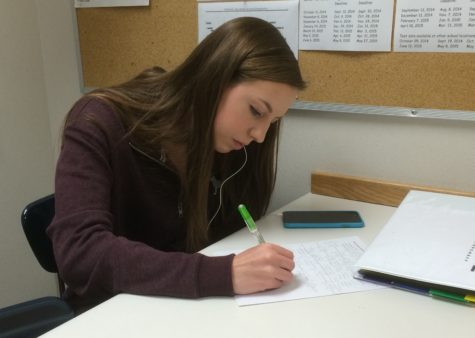"Katie Popcheff, nurses' aide and senior, works on homework during her period as a nurses' aid. Popcheff said, ""(The nurses) don't have us run passes very often, so I just work on homework."""