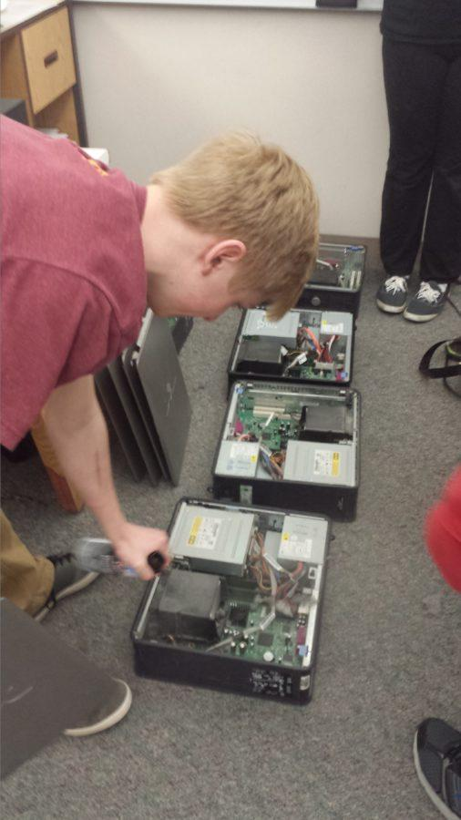 Jack Kelley, Computer Building Club member and junior, cleans the dust out of computers. This cleaning is a part of the computer refurbishing process.
