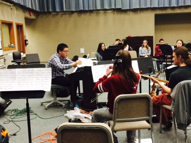"""While rehearsing the program for the Music for Miracles concert, senior YiChang """"Yi"""" Cui conducts the Carmel Electric Ensemble.  The ensemble will preform at the Palladium on May 8."""
