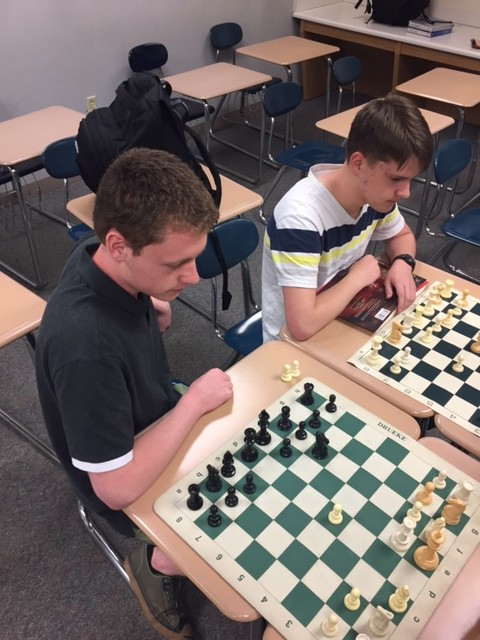 """Chess Club memebers, junior Mikel Frausto and sophomore Caleb Smith, play two-on-two chess together. """"I'm really going to miss the club and how we can all come in to just play chess,"""" Frausto said."""