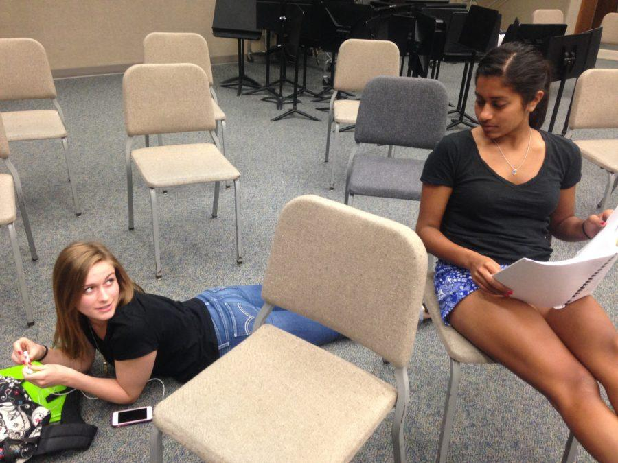 Mary Woods (left) and Sharmistha Chakrabarti (right), Philharmonic Orchestra members and seniors, do their homework in the orchestra SRT. As a senior, Woods said she is sad that she will no longer be playing music with her friends that she has known for a long time when the school year ends.