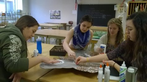 Art Club members glue pennies to the butterfly sculpture. Bubp said Art Club will install the sculpture in the Arts Garden upon completion. JESSICA MO/PHOTO