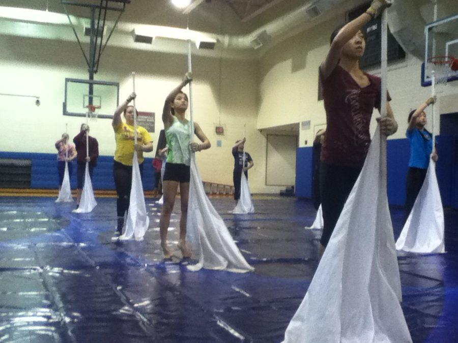 +Color+Guard+members+stand+in+position+during+their+morning+practice.+They+will+be+performing+in+the+WGI+World+Championships+in+mid-April.