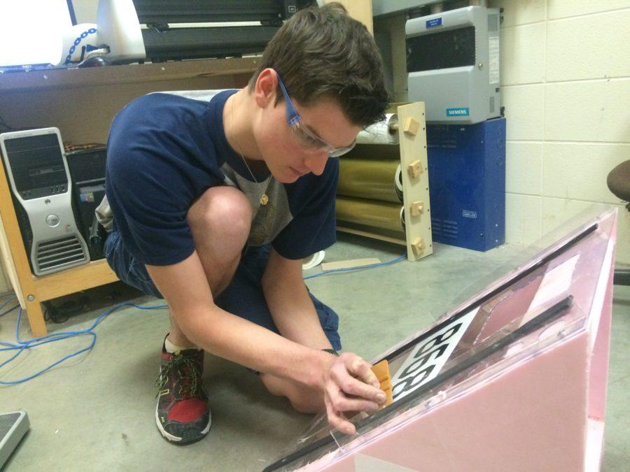 Blake Loncharich, TechHOUNDS student team leader and senior, applies vinyl to the human player station ramp. The team plans to practice with the ramp and take it tothe state competition on April 2. JESSICA TAO / PHOTO