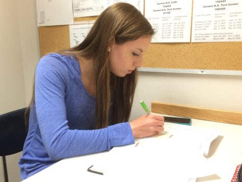 "Katie Popcheff, nurses' aide and senior, works on homework during her period as a nurses' aid. Popcheff said, ""I've run a couple passes, but most recently it hasn't been too busy in the health center."""