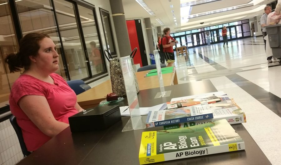 In the main cafeteria, NHS Member Katie Boynton sells prep books at a booth. The prep book sale started last week and will run until the end of next week.