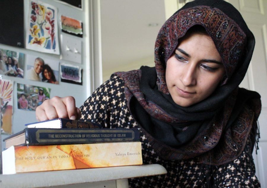 Senior Mehar Athar looks at her collection of Islamic religious texts which outline the beliefs of her religion. While identifying as a Muslim, Athar said she believes people should make conscious social decisions based on their own beliefs before integrating their own beliefs. Swetha Nakshatri / Photo
