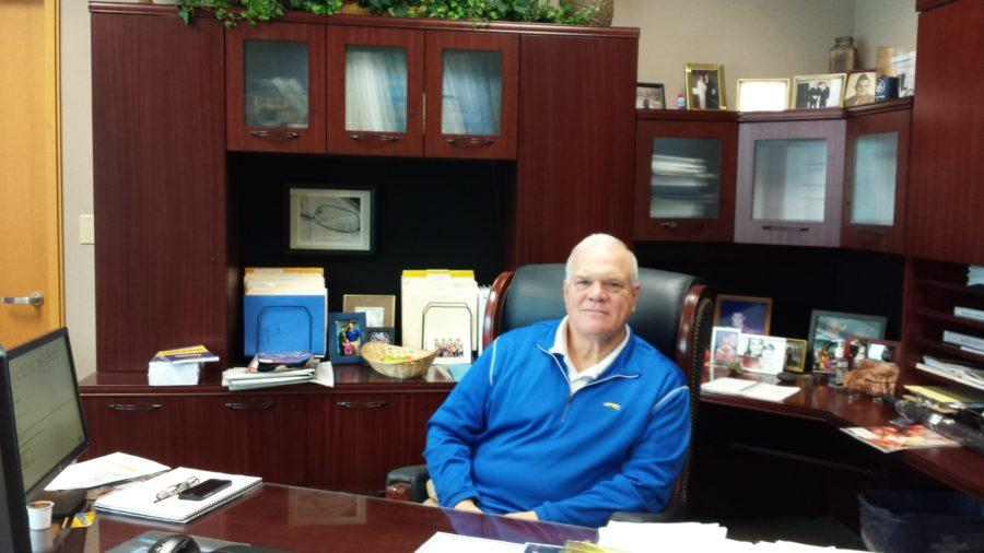 """Principal John Williams works at his desk in the main office. CHS administrators recently released a new final exam schedule that """"office hours,"""" three-hour periods during which students can choose to come to school for help from teachers."""