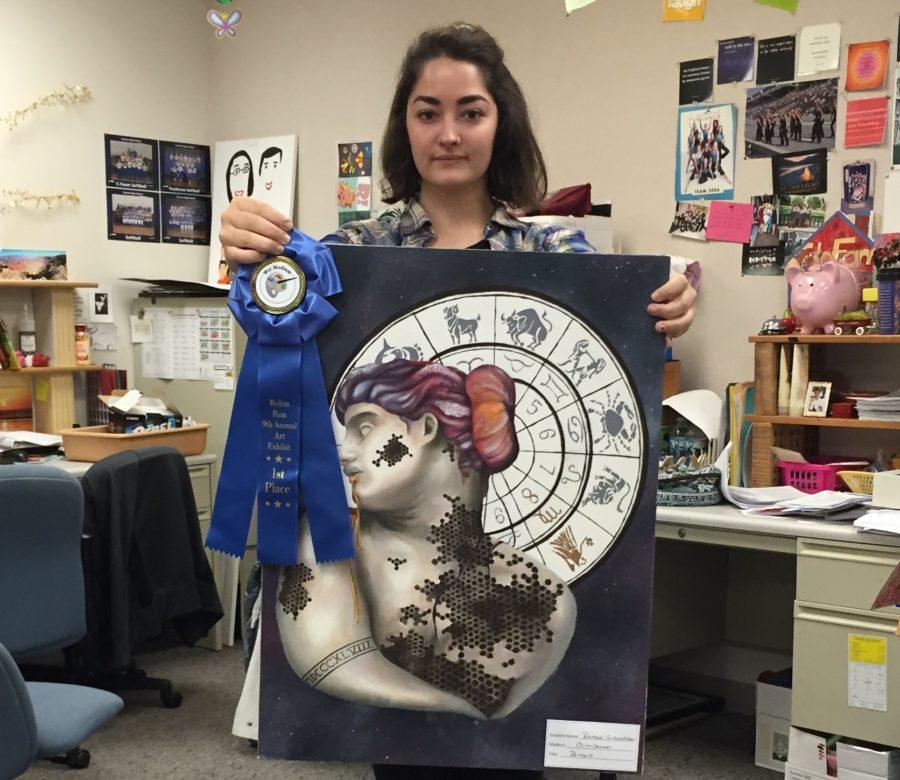 Senior Rachel Seidensticker shows off her award-winning surrealist style painting. Seidensticker will showcase her piece in the Carmel International Arts Festival this weekend. LILLY ST. ANGELO / PHOTO