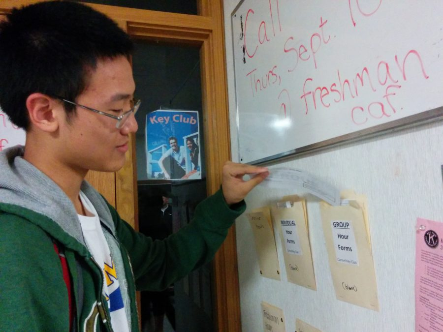 Nathan Fei, Key Club member and junior, takes a volunteer hours form to record his community service on. Club members who volunteered over the summer can get a maximum of 10 volunteer hours for their work.