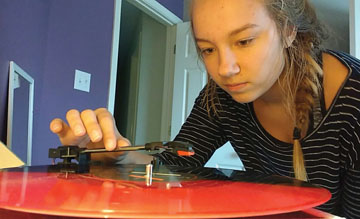 Sophomore Carly Colbert plays one of her vinyl records. Vinyl records have risen in popularity in recent years since they're seen as 'vintage' and 'hipster.'' REBECCA QIN // PHOTO