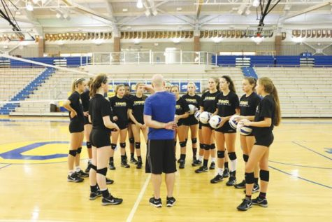 HUDDLE UP: Head women's volleyball coach, Matt Fishman, discusses strategy with his players. The women's volleyball team is one of the many female teams at CHS with a male coach.