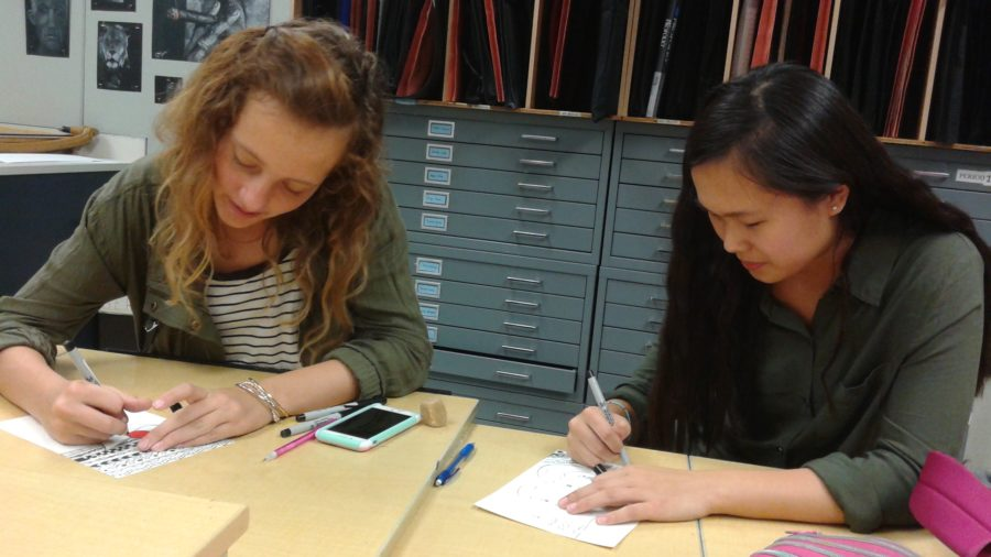 """Marlie Mehrtens and Sophie Wang, Art Club members and freshmen, work on """"Zen Doodle"""" Christmas-themed cards for the silent art auction during Art Club's Oct. 8 meeting. Art Club will donate money from the auction to food pantries. JESSICA MO / PHOTO"""