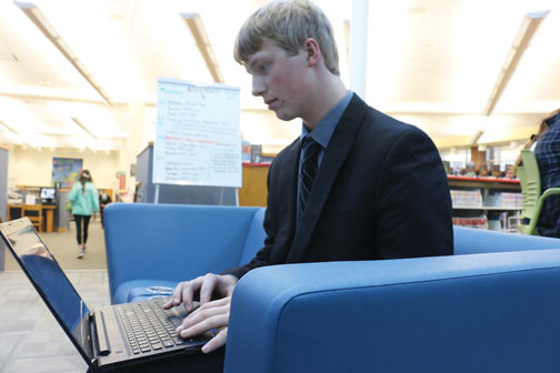 """CHECKING OUT: Christopher """"Chris"""" Coraggio, independent study student and senior, works on his laptop for his independent study in the media center. Coraggio said he has seen a notable increase in the use of electronic resources instead of physical books."""