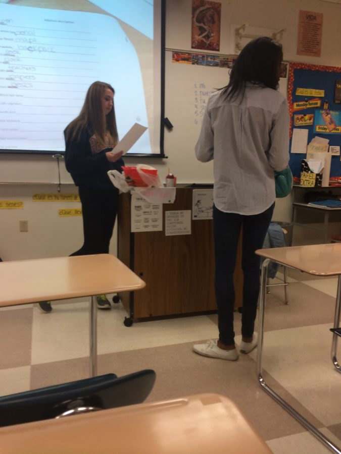 """Katie Roebuck, Spanish club co-president and junior, discusses the plans for the Nov. 9 meeting. During the meeting, Spanish club member colored in sugar candy skulls and watched """"The Book of Life."""" SABRINA MI / PHOTO"""