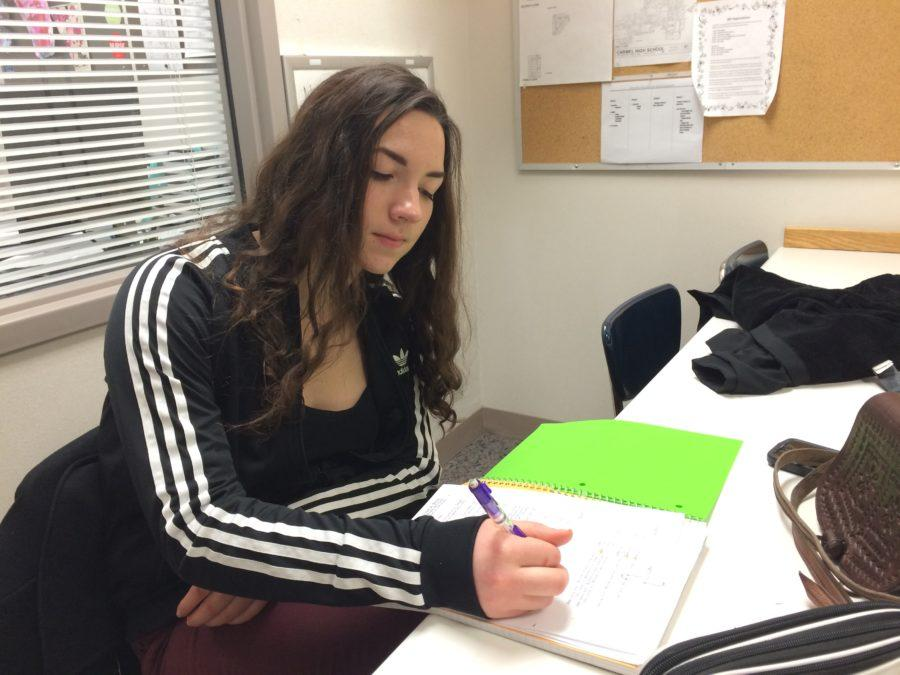 """Nurses' aid Katie Tellus works on her homework in the health center. Tellus said, """"For a normal period (in the health center)…, we come in and do our homework. If anything is asked of us, like to bring passes (to students), then we go do it."""""""