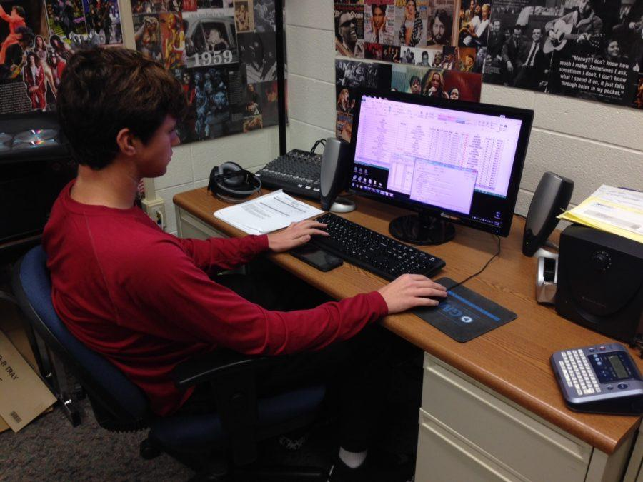 WHJE member and junior Zach Miller chooses new songs for the radio station to play. Miller said he was looking forward to submitting entries for the IASB contest in March. PHOTO/ MATTHEW ZHENG