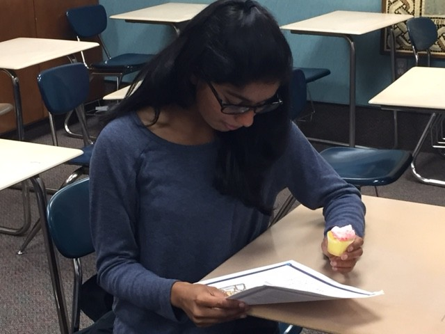 """(Sanyukta) Mili Das, club member and sophomore, snacks on club cupcakes while reading the meeting's syllabus. """"I think Latin sounds so beautiful when spoken, and it's also really fun to learn more about Latin and hang out with my friends,"""" she said. PHOTO/ GRACE ZHANG"""
