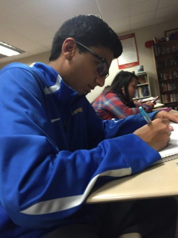 Senior Senator Neil Shah reviews his notes during AP Government class. Shah said he is looking forward to seeing everyone dressed up in disco clothing at the disco dance on Jan. 22. PHOTO/ EMMA LOVE