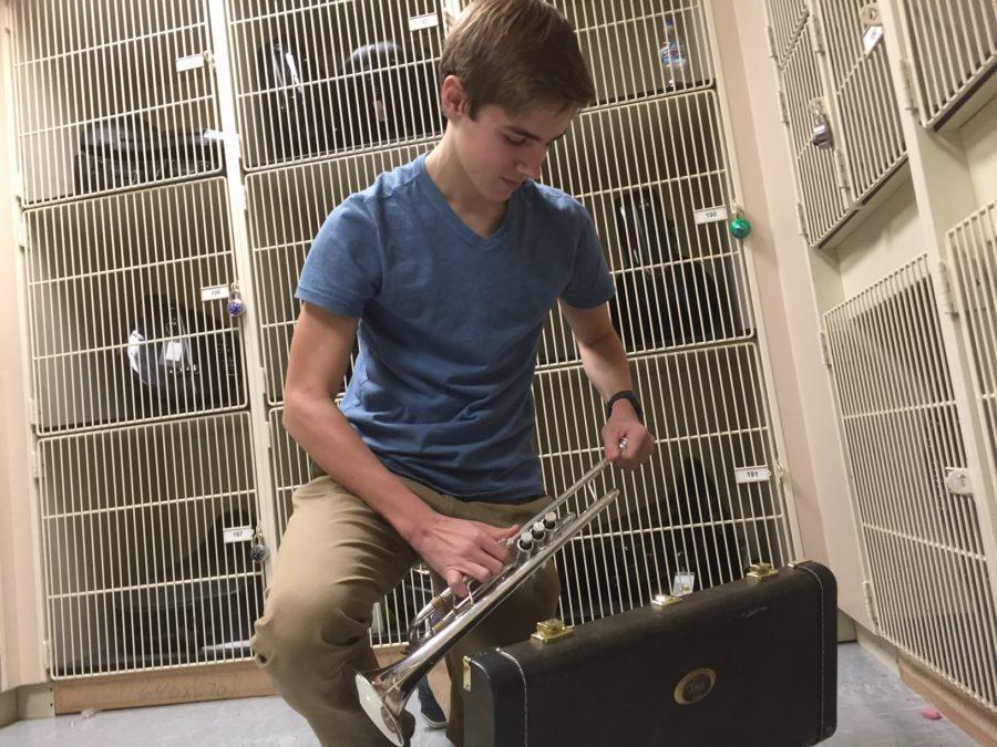 Alex Fleig, Jazz I Ensemble trumpet player and senior, assembles his trumpet in the band storage room. Fleig said his favorite Jazz Ensemble event is Jazz a la Mode. PHOTO/ KATIE LONG