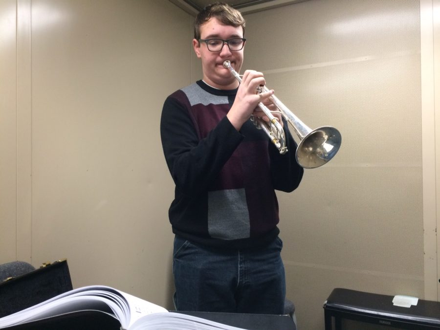 avier Searle, trumpet player for Jazz Ensemble 1 and junior, warms up in a practice room. Searle said he participates in Jazz Ensemble because he aspires to be a jazz trumpet player when he grows up. PHOTO// KATIE LONG