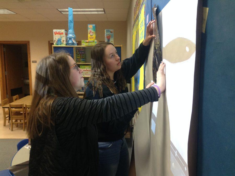 Makela Kaopuiki and Maggie Hettiger, student teachers for Kids' Corner and seniors, make bulletin boards for Kids' Corner.