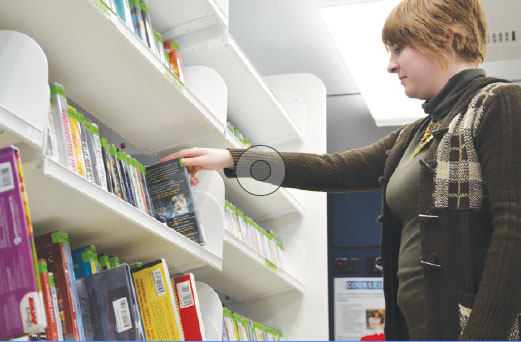 CHECKING IT OUT: Mobile librarian Kasey Courter replaces a book from the mobile library's collection. The mobile library carries best-selling books, as well as those most checked out at the main building. SHREERAM THIRUNAVUKKARASU // PHOTO