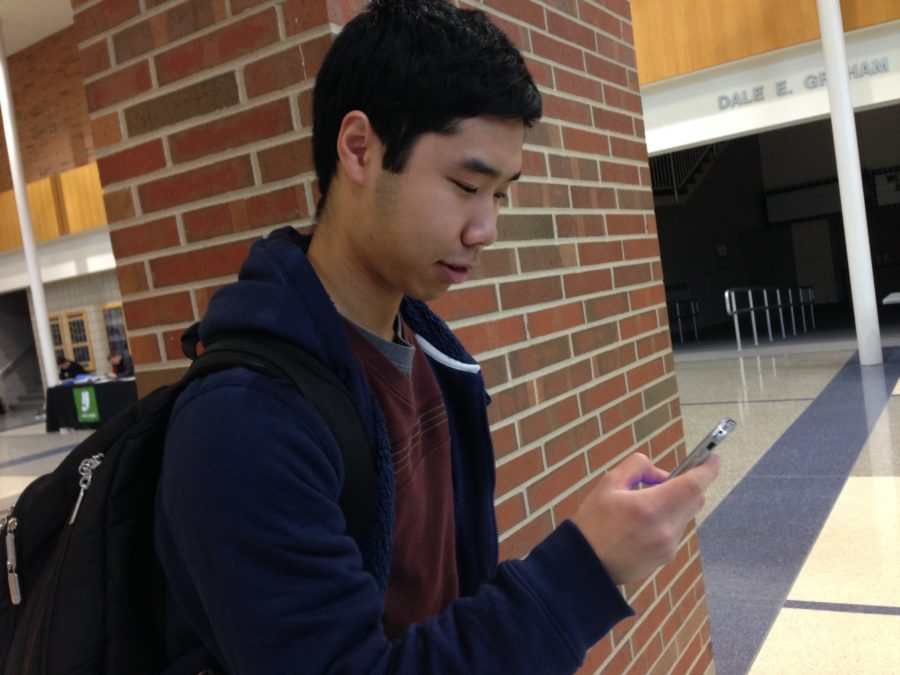 Senior Ryan Jou checks his phone in the commons area. Jou said he believes the proposed bus driving plan will be helpful to hire new bus drivers.