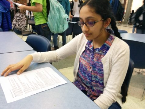Srijana Chavali, Key Club member and freshman, reads a club meeting agenda. Club sponsor Katie Kelly said students should find volunteer opportunities, which are listed on agendas, so they can meet volunteer hour requirements before the end of the semester.