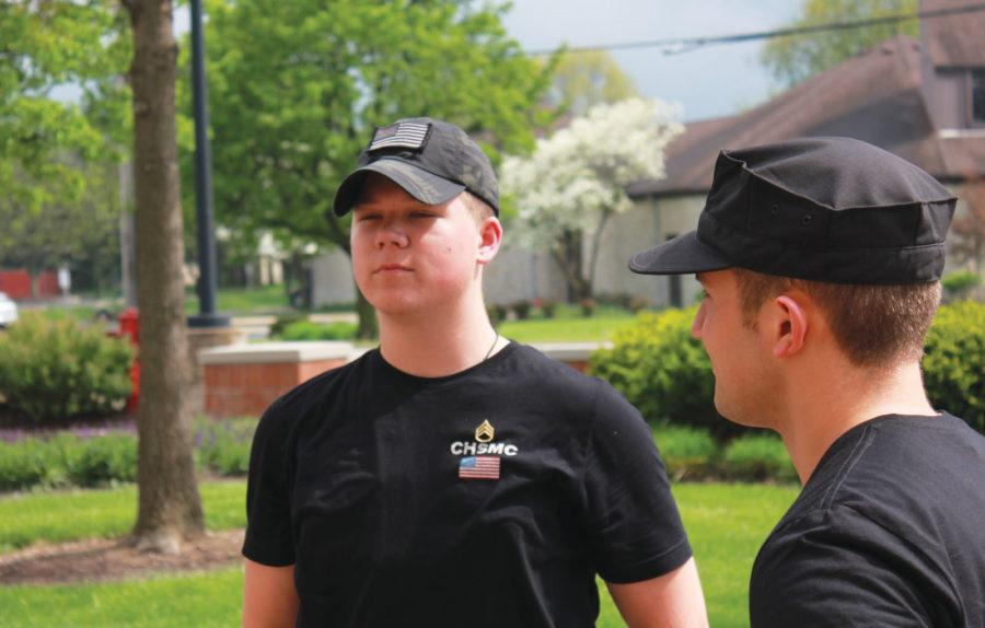 """MAJORING IN THE MILITARY: Zach Rogers, Military Club member and senior, stands during a Military Club meeting while former club officer, Joseph """"Joe"""" Fletcher '16 watches on. Rogers said his parents are proud of him for wishing to join the Marines. NYSSA QIAO // PHOTO"""
