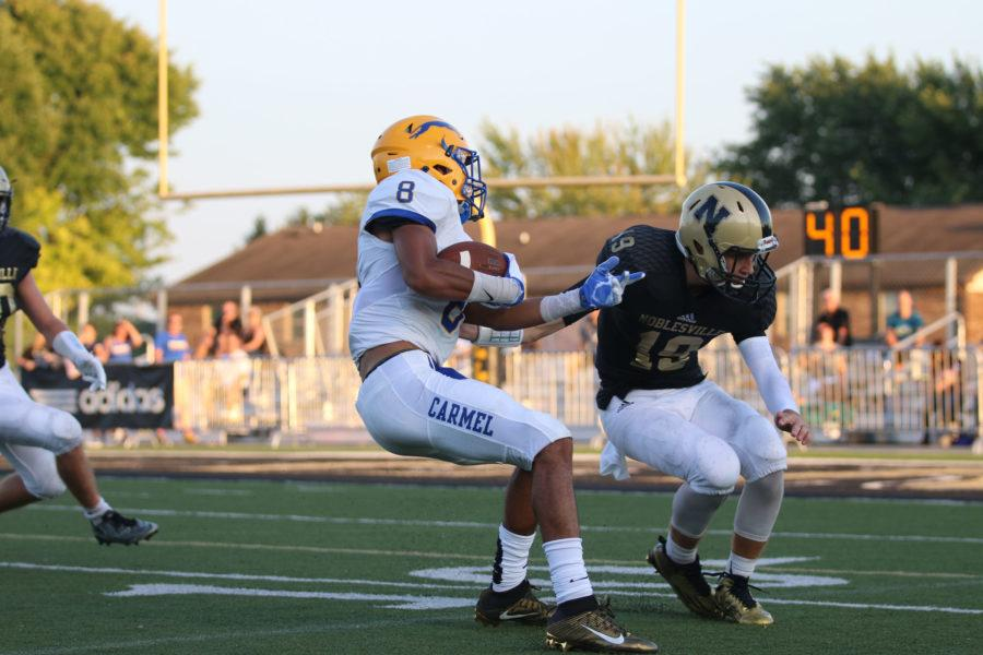 Ethan Merriweather, wide receiver and senior, makes a move around a Noblesville High School defender during the game on Aug. 27. CHS won the game 24-9.