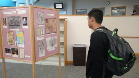 Sophomore Joseph Hsu reads the new exhibit in the Media Center. According to John Shearin, these exhibits usually coincide with what freshman classes are learning about.