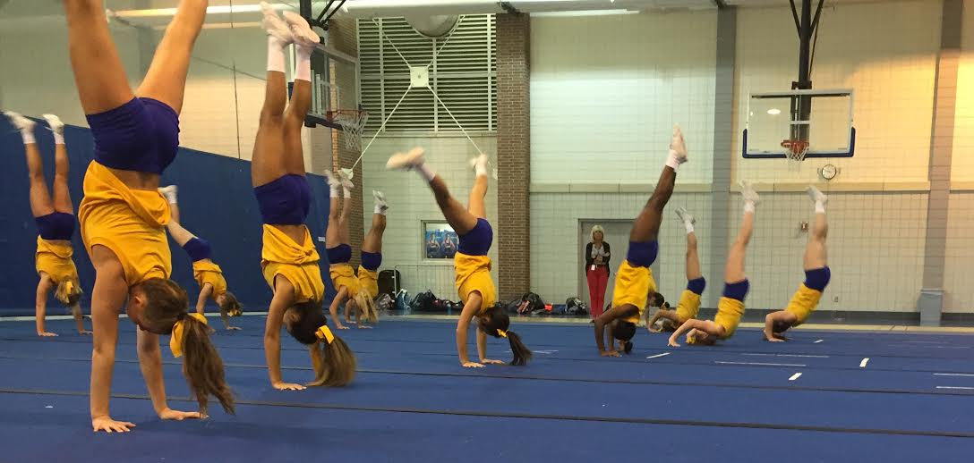 The cheerleading team warms up at practice by going through tumbling lines. They won their last competition at the Kentucky State Fair, and continue to prepare for their next.