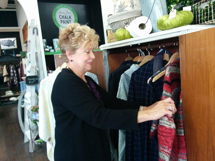 Susan Jabaras, manager of clothing and furniture store ReStyled, stocks sweaters in preparation for fall. Many other Carmel stores like Highgarden Real Estate are also preparing for fall holidays, such as hosting events like trick-or-treating.