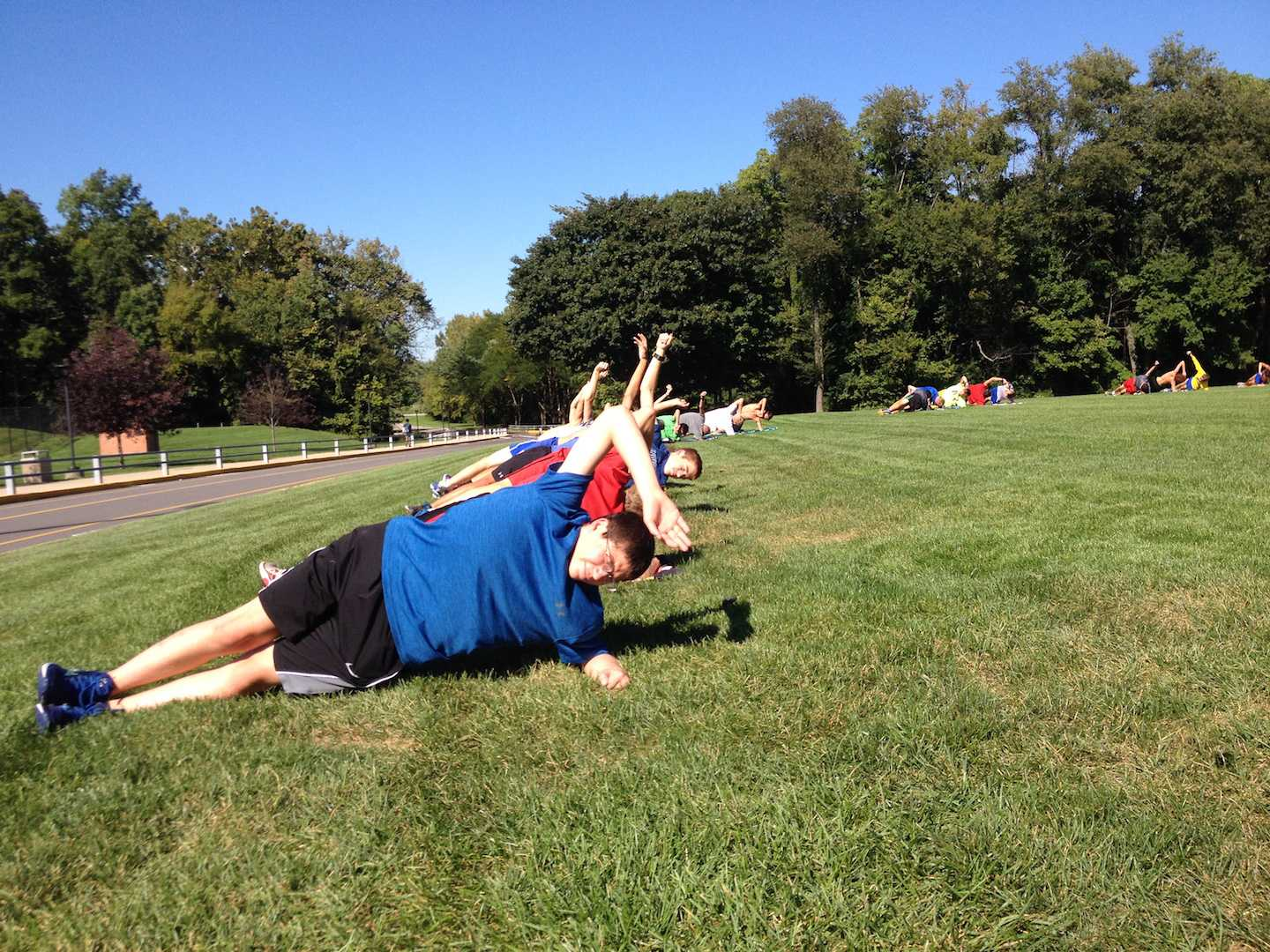 Sophomore Adam Ratzma practices core exercises with the rest of the team during the beginning of a practice. The next meet is on Oct. 8 at White River Elementary.
