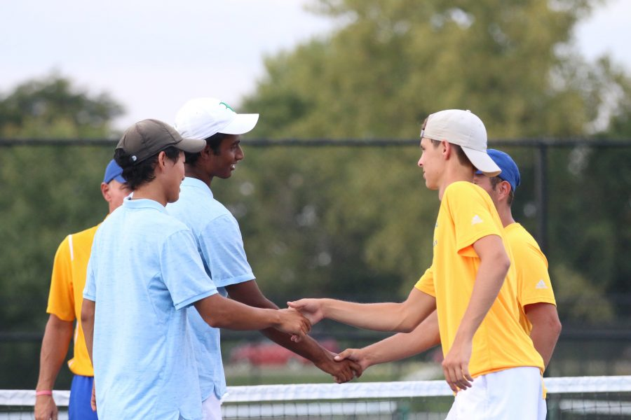 Mark Zhang and Rohit Nagaraj, varsity tennis players and seniors, shake hands with their opponents from Homestead on Sept. 23. The men's tennis team will be playing for their seventh consecutive Semi State title at Culver on Oct. 8.