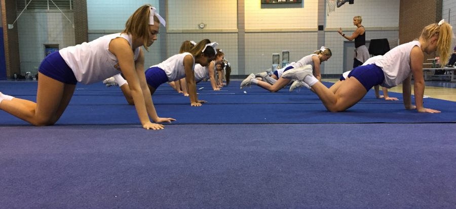 Varsity+Cheerleading+stretches+before+practice.+Before+the+team+starts+practice%2C+the+cheerleaders+change%2C+roll+out+the+mats%2C+and+then+take+time+to+stretch+during+their+warm+up.+