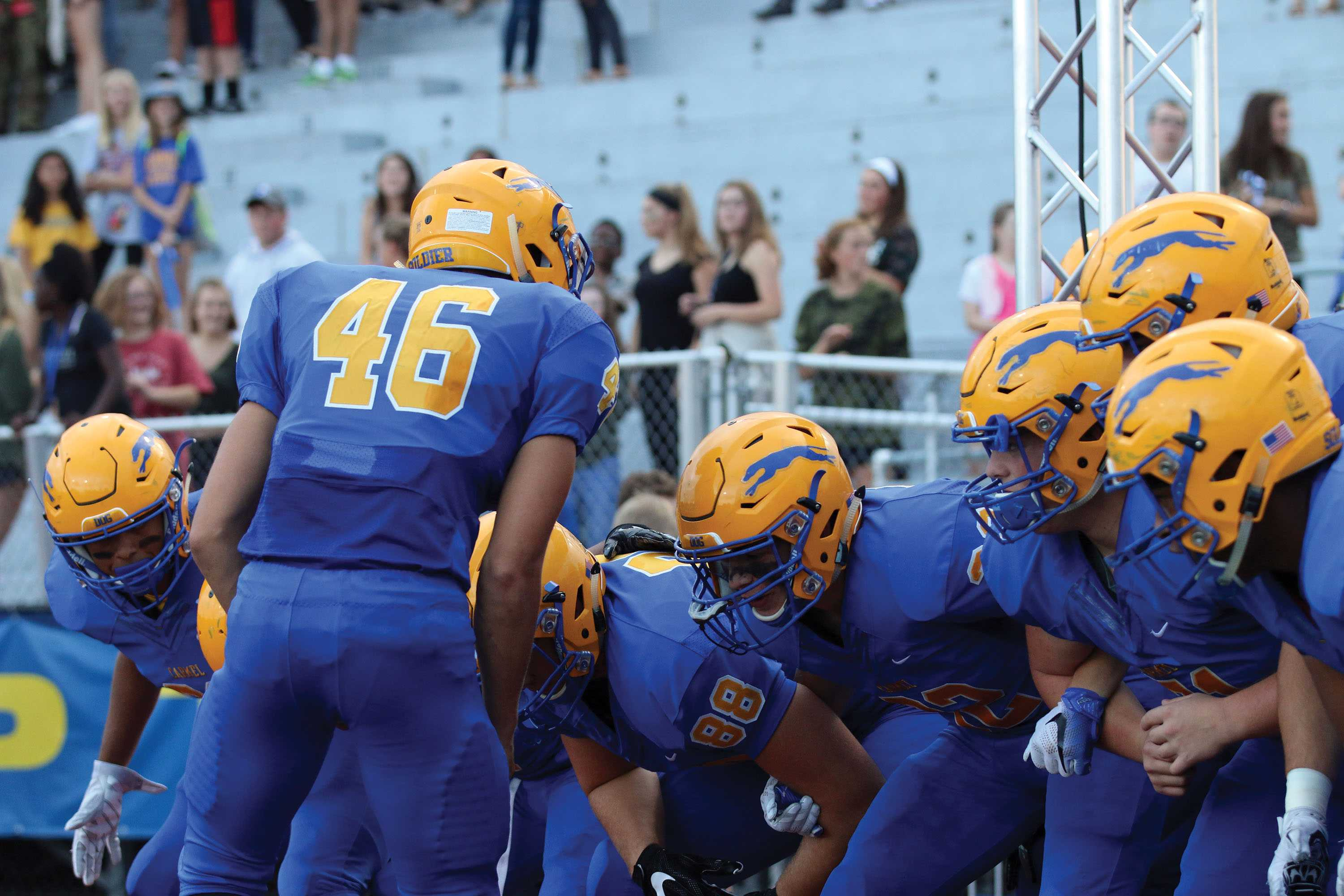 """PREGAME PREP: The CHS football team huddles before a game in the tunnel and prepares by getting motivated. Before every home game the team walks out of the locker room, stands in a huddle then stampedes on to the field as cheerleaders run with flags that spell out """"Carmel."""" This is one of the many traditions the CHS football team has. Others include a team dinner the day before games and also cheering the CHS fight song after finishing the game."""