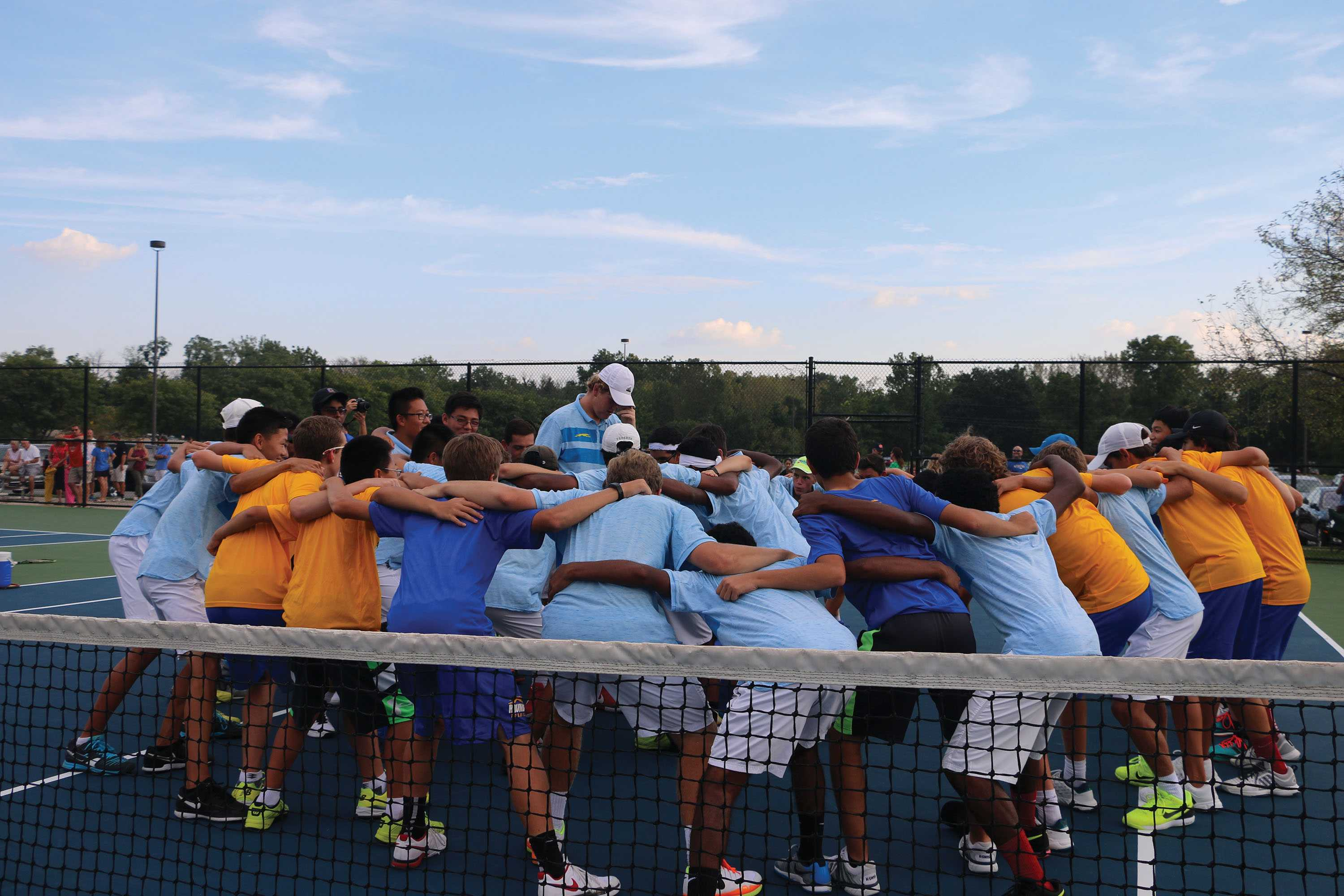 """TENNIS TOGETHERNESS:  The tennis team huddles together before a match against Homestead High School. Ethan McAndrews, varsity tennis player and senior, said, """"Before we go out and play, we all get in a circle together and break it down as a team."""" McAndrews said it gets the team motivated and also assists in the focusing of the team."""