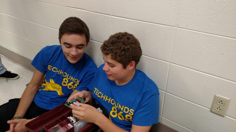 Caleb Smith, TechHOUNDS member and junior, and Derek Fronek, TechHOUNDS member and sophomore, examine a piece of hardware in the industrial technology (I.T.) hallway. Smith, Fronek and other TechHOUNDS members are seeking sponsorships from local businesses to pay for the TechHOUNDS season.​