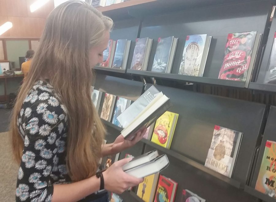 A CHS student scans a book in the Young Adult section of the Carmel Clay Public Library. The library offers many services besides just book checkout, including study areas, computers and the library café.