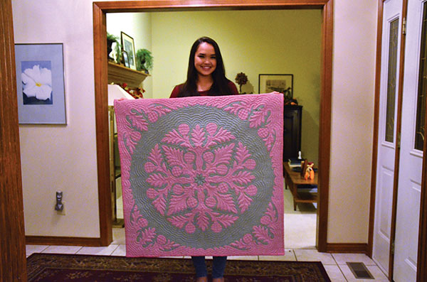 "Hawaiian and Junior Catherine ""Kate"" Adaniya holds a family blanket. The pattern on the blanket represents many beliefs and traditions in Hawaiian culture."