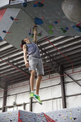 JUST HANGING OUT: Hoosier Heights employee Noah Novak hangs from a climbing hold. The Hoosier Heights gym has different rock walls and an American Ninja Warrior course. The rock walls include both free climbing and belay climbing. MICHAEL JOHNSON | PHOTO