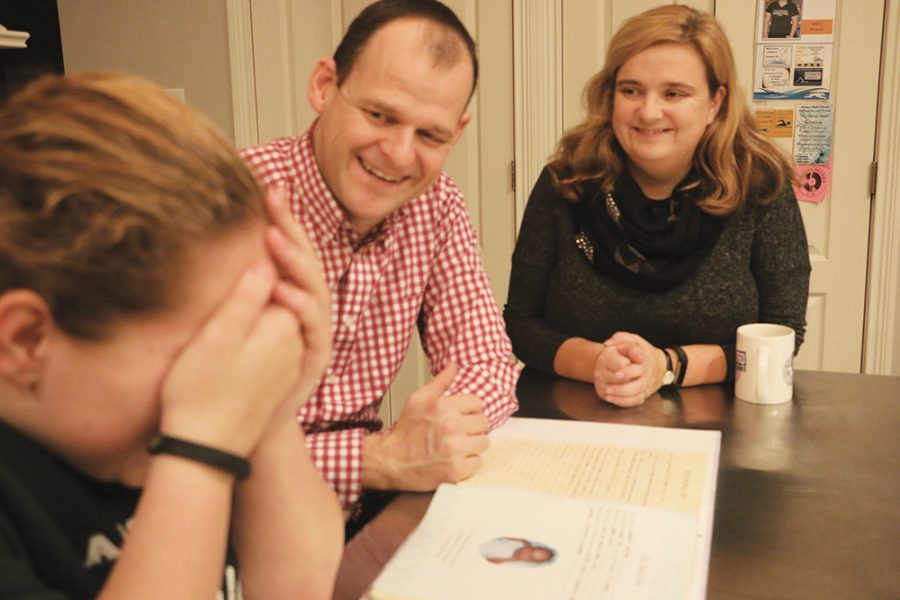 A DIFFERENT LIFE: Sophomore Abby Draper reflects on her life after adotion by looking through her baby photos with her adoptive parents. She said she wishes to find her birth parents when she turns 18 years old.
