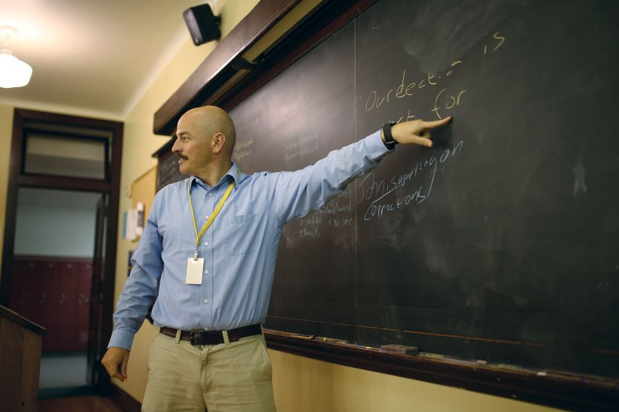 THIRD-PARTY THINKING:  Government teacher Joshua Miller gestures toward his classroom's blackboard. Miller said there were too many obstacles for third-party candidates in U.S. elections.